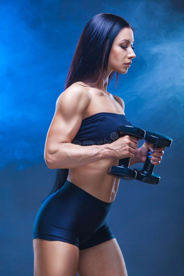 Athletic young woman doing a fitness workout with dumbbells on black studio background. Around the shrouds the model stock photos