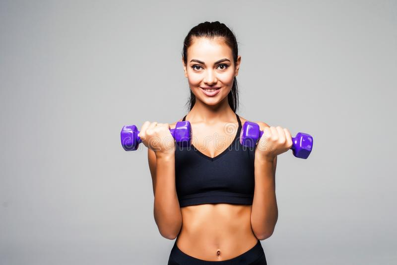 Athletic young woman doing a fitness workout with dumbbells on grey background royalty free stock photo