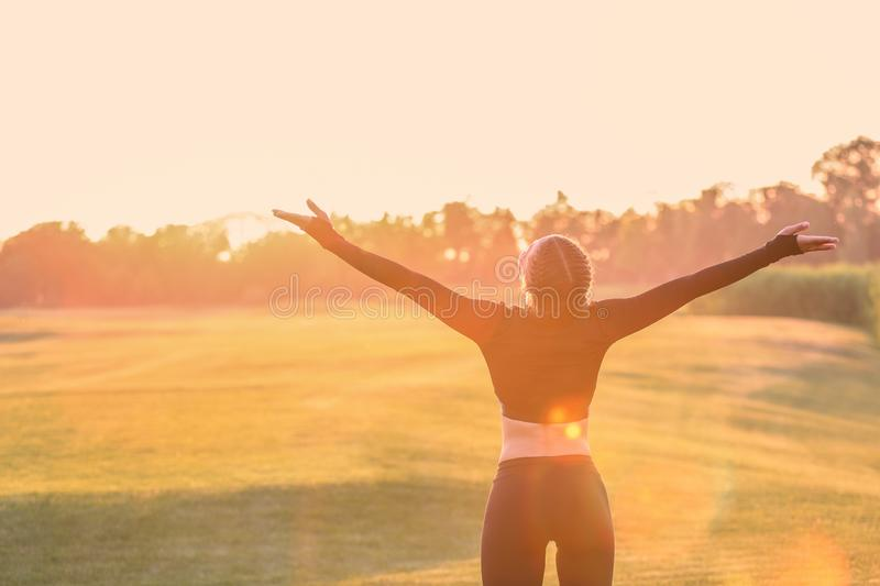 Athletic young woman enjoying nature at sunrise royalty free stock photography