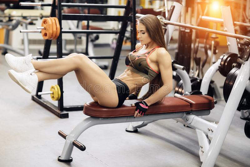 Athletic young woman exercises for abs on the bench press. stock photos