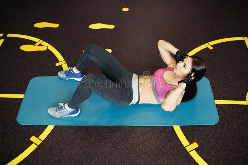 Athletic young woman exercises abs ont he fitness mat. Athletic young woman exercises abs ont he fitness mat stock images