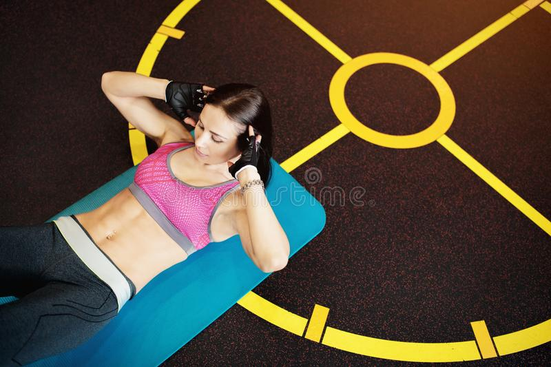 Athletic young woman exercises abs ont he fitness mat. Athletic young woman exercises abs ont he fitness mat royalty free stock photos