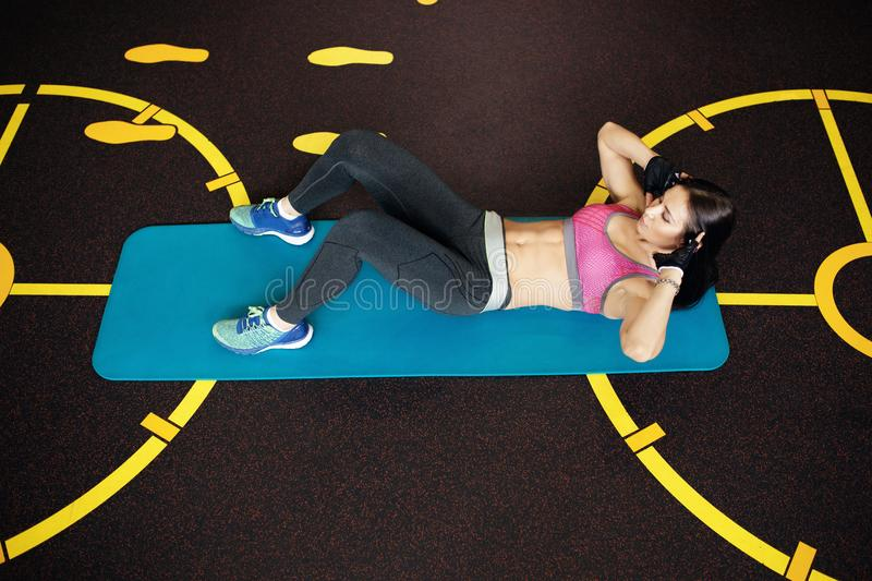 Athletic young woman exercises abs ont he fitness mat. Athletic young woman exercises abs ont he fitness mat royalty free stock photo