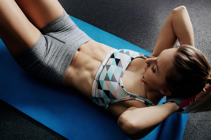 Athletic young woman exercises her perfect abs on the fitness mat in the gym or yoga class. stock photo
