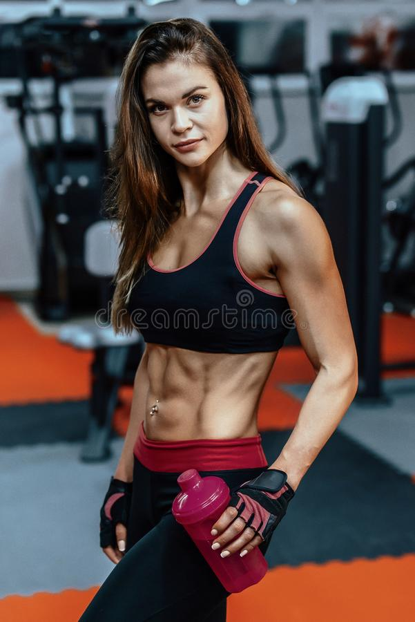 Athletic young woman after hard workout at gym. Fitness girl holds shaker with sportive nutrition. royalty free stock images