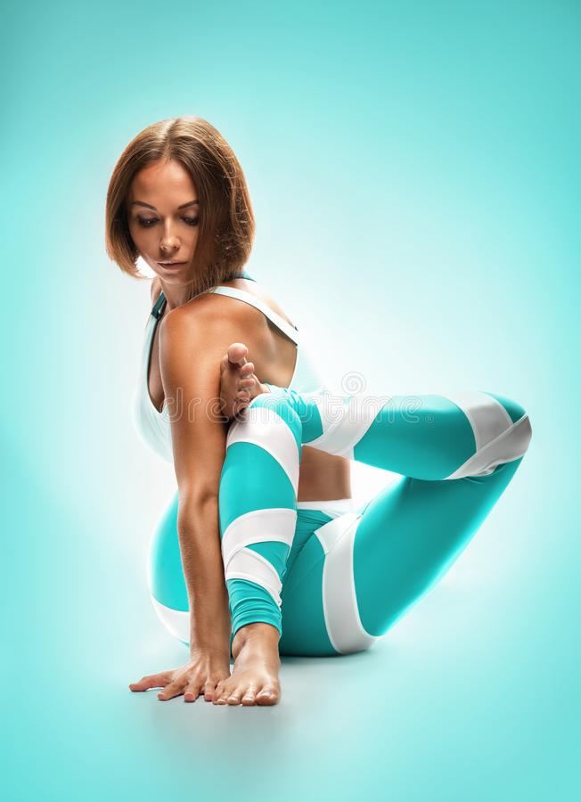 Athletic young woman practicing yoga on turquoise background. royalty free stock image