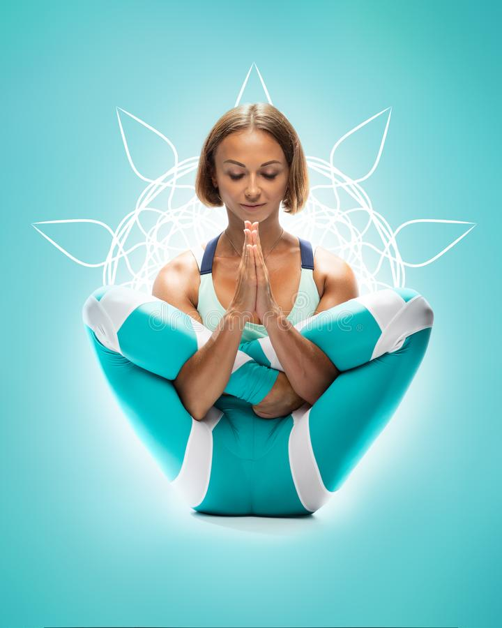 Athletic young woman practicing yoga on turquoise background with beautiful white mandala. Girl focused on practice. Complex asana royalty free stock photography