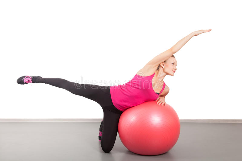 Athletic young woman with red ball. On the floor stock photography