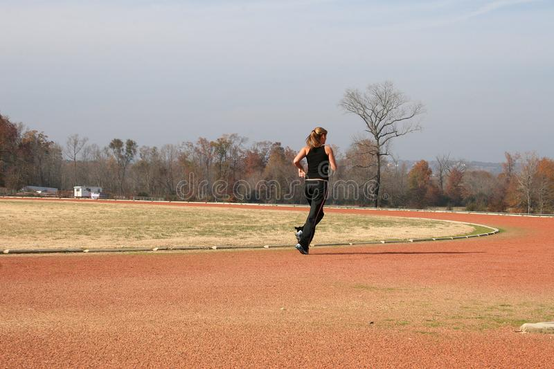 Athletic Young Woman Running at the Track stock photography