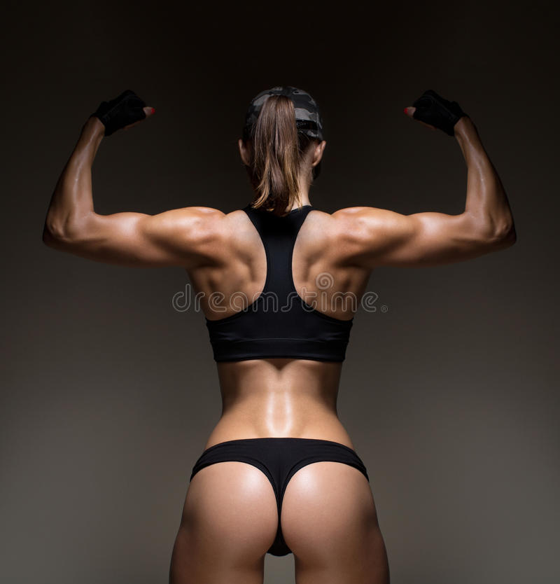 Athletic young woman showing muscles of the back. And hands on a isolated black background with clipping path royalty free stock photos