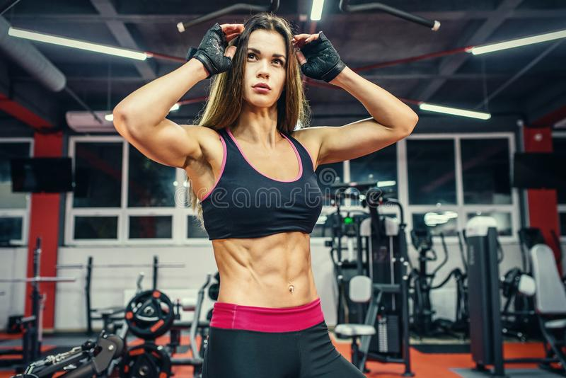 Athletic young woman showing muscles after workout in gym. stock photos