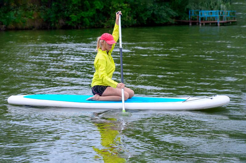Athletic young woman sitting with a paddle on a river, Active healthy vacation concept stock photos