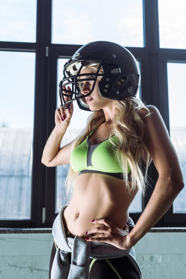 athletic young woman in sport bra and american football helmet looking stock image