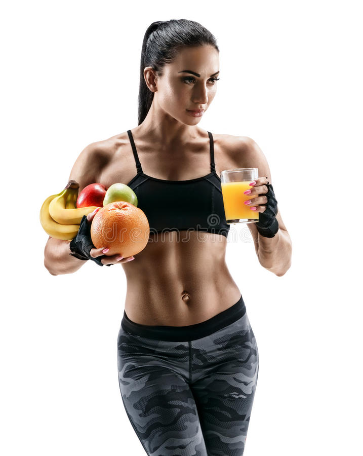 Athletic young woman in sports wear hold fresh fruits and glass orange juice. royalty free stock photography