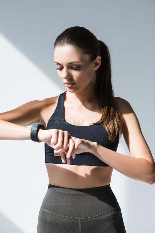 athletic young woman in sportswear using smartwatch stock photography