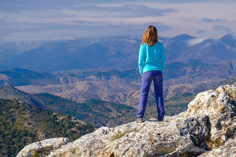 Athletic young woman standing on the rocky top of the mountain against the blue sky royalty free stock photography
