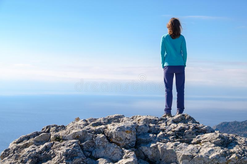 Athletic young woman standing on the rocky top of the mountain against the blue of sky and sea. Back to the camera royalty free stock photos