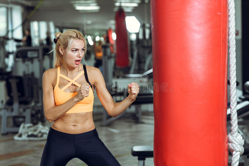 Athletic young woman training with punching bag at gym royalty free stock photos