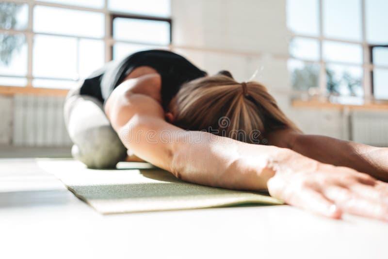 Athletickwoman joven que hace ejercicio de la yoga en la estera de la aptitud en el gimnasio soleado blanco morling temprano fotos de archivo