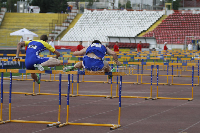 Athletics discipline - 100 metres hurdles. Male competitors performing during the 100 metres hurdles discipline at Romanian International Atheltics Championship royalty free stock photography