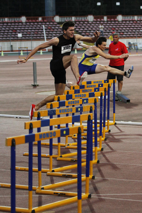 Athletics discipline - 100 metres hurdles. Male competitors performing during the 100 metres hurdles discipline at Romanian International Atheltics Championship royalty free stock images