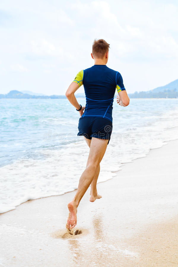 Athletics. Fit Athlete Jogger Running On Beach. Workout. Sports, Fitness. Athletics. Fit Athlete Male Jogger Running On Beach. Athletic Sporty Man Jogging On royalty free stock photography