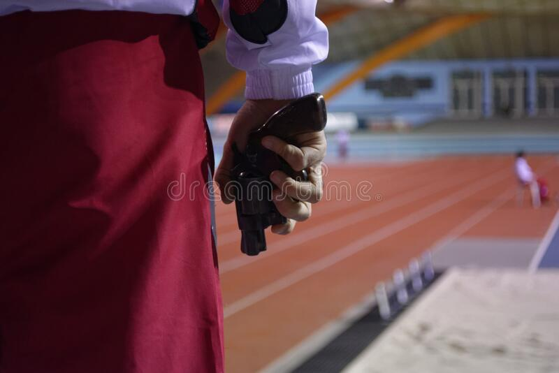 Athletics race referee with his instrument. The athletes are at the sound of the referee`s shot and then the competition starts royalty free stock photo