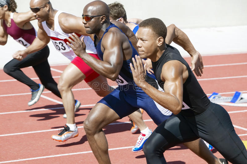 Athletics Sprinting On Running Track. Side view of multiethnic male athletics sprinting on running track royalty free stock images