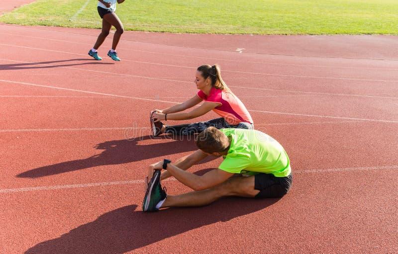 Athletics warming on the track. Couple on stadium athletics warming stock photography