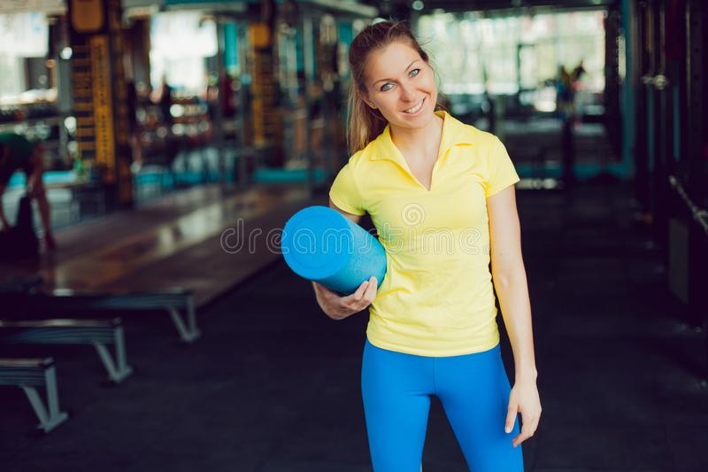Athletics. Young female athlete with a Mat for stretching in the hands stock images