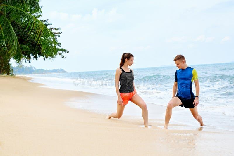 athletik Geeignetes Paar-Ausdehnen, trainierend auf Strand Sport, F lizenzfreie stockfotografie