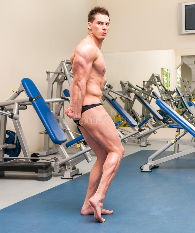 Athletisch errichteter Sportler in der Turnhalle stockbild