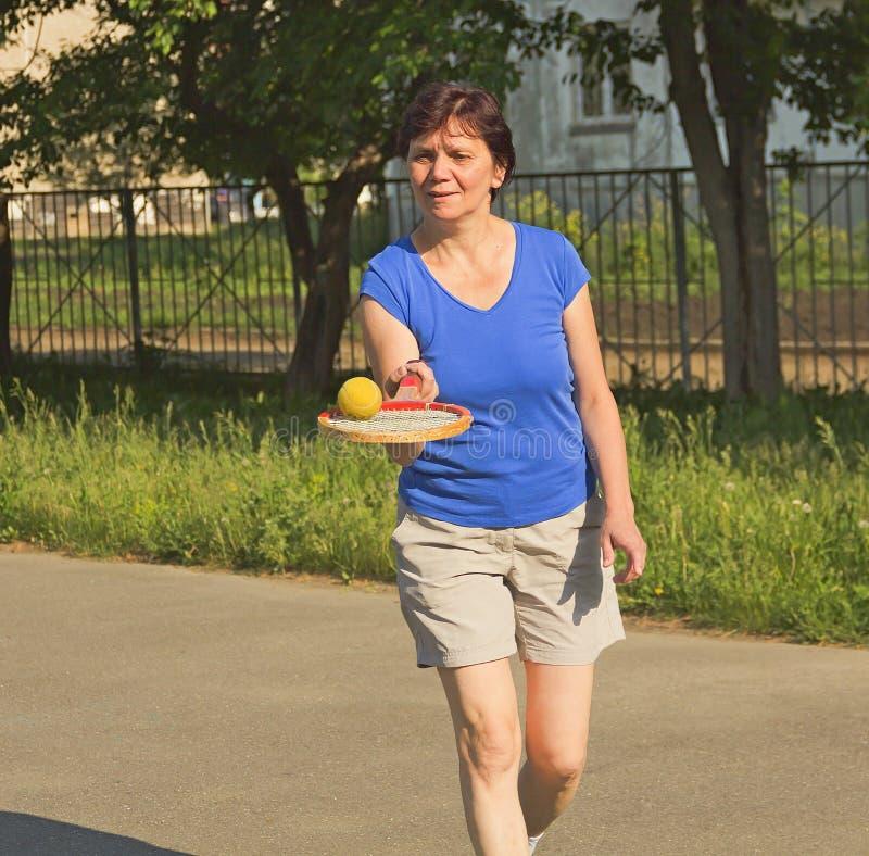 Athletische ältere Frau, die einen Tennisball anfüllt lizenzfreie stockfotografie