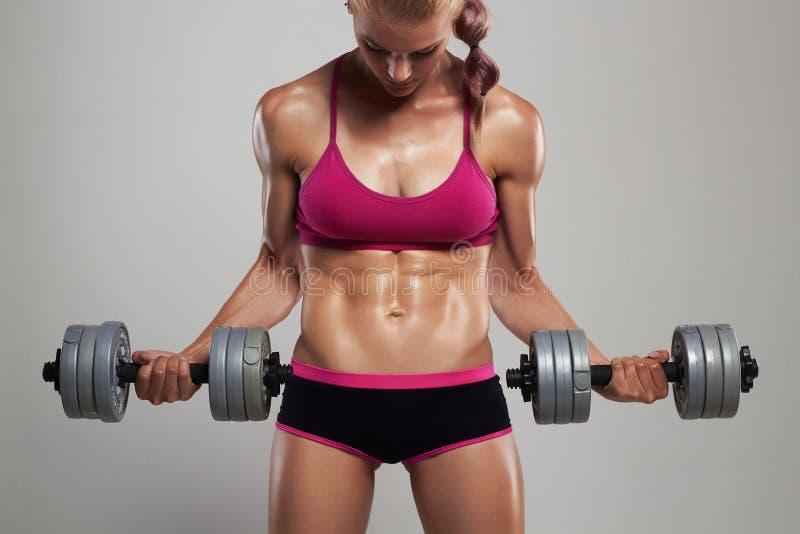 Athletische Bodybuilderfrau mit Dummköpfen schönes blondes Mädchen mit den Muskeln lizenzfreies stockbild