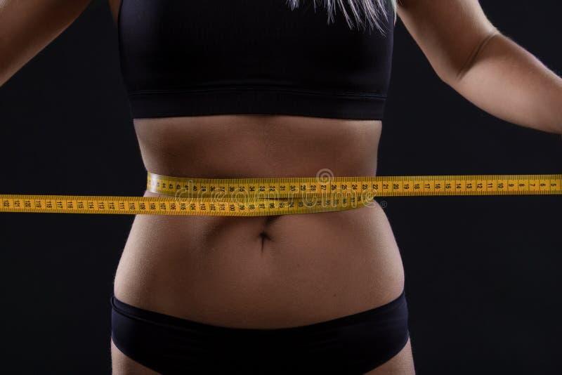 Athletische dünne Frau, die ihre Taille durch Maßband nach einer Diät über schwarzem Hintergrund misst stockfotografie