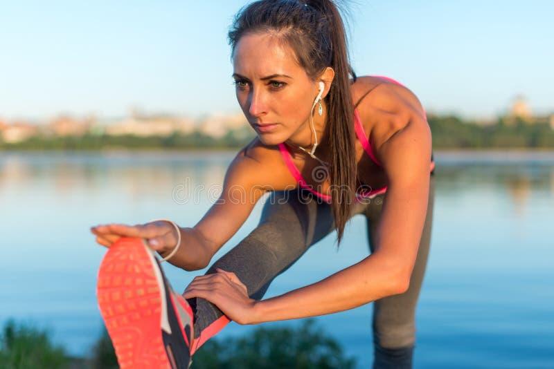 Athletische Frau, die ihre Kniesehne, Beinübungs-Trainingseignung vor Training draußen auf einem Strand am Sommerabend mit h ausd stockfotos