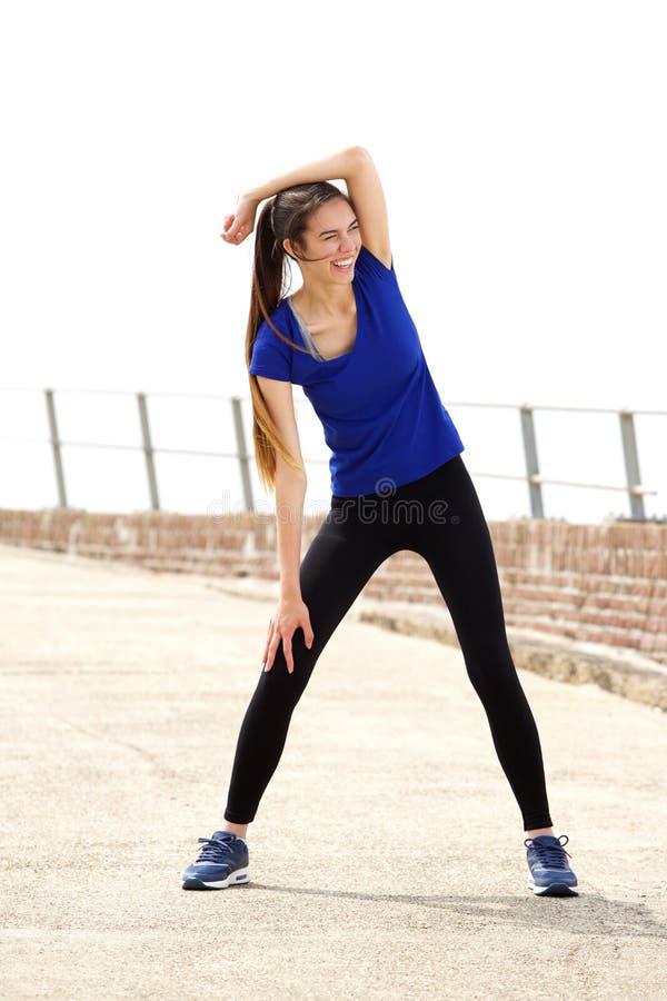 Athletische Frau, die mit dem Arm angehoben ausdehnt lizenzfreies stockbild