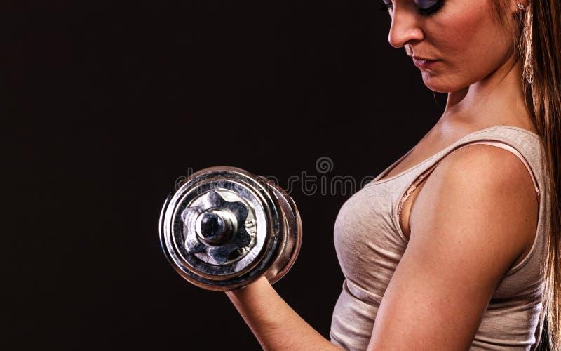 Athletische Frau, die mit schweren Dummköpfen arbeitet stockfoto