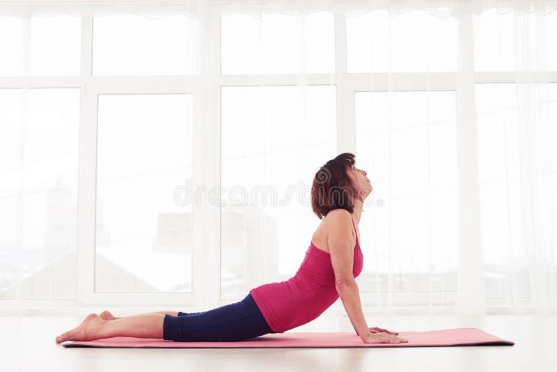 Athletische Frau, die an Yogaübung bhujangasana oder Kobrahaltung tut stockbilder
