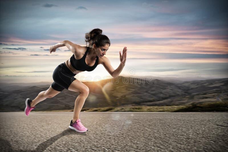 Athletische Frau läuft auf der Straße während des Sonnenuntergangs stockbild