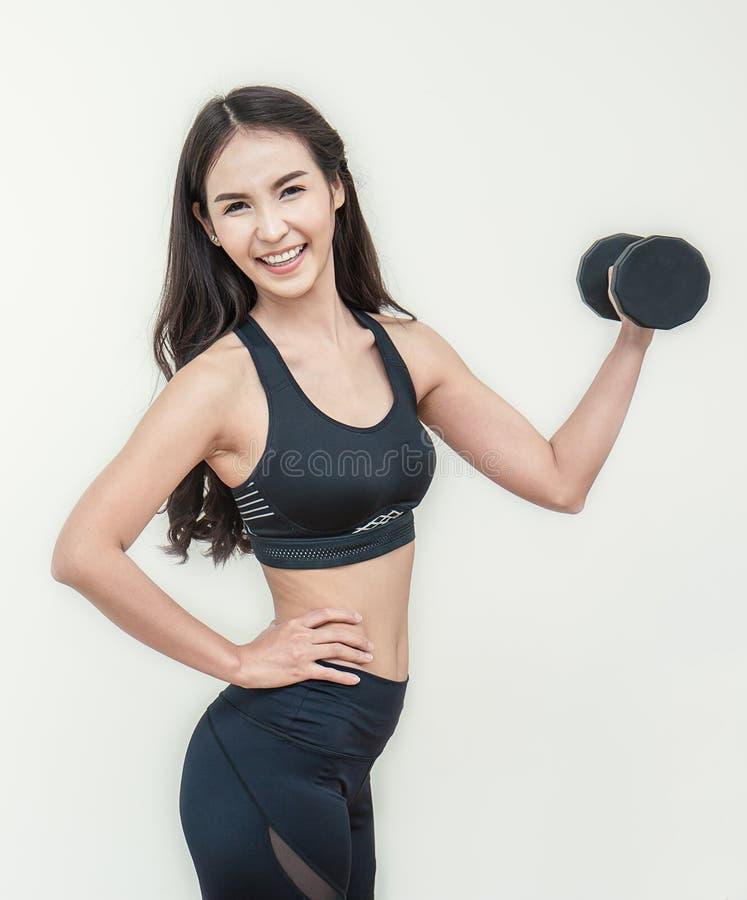 Athletische junge asiatische Frau, die Bizeps zeigt lizenzfreie stockbilder