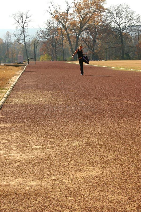 Athletische junge Frau, die an der Bahn ausdehnt