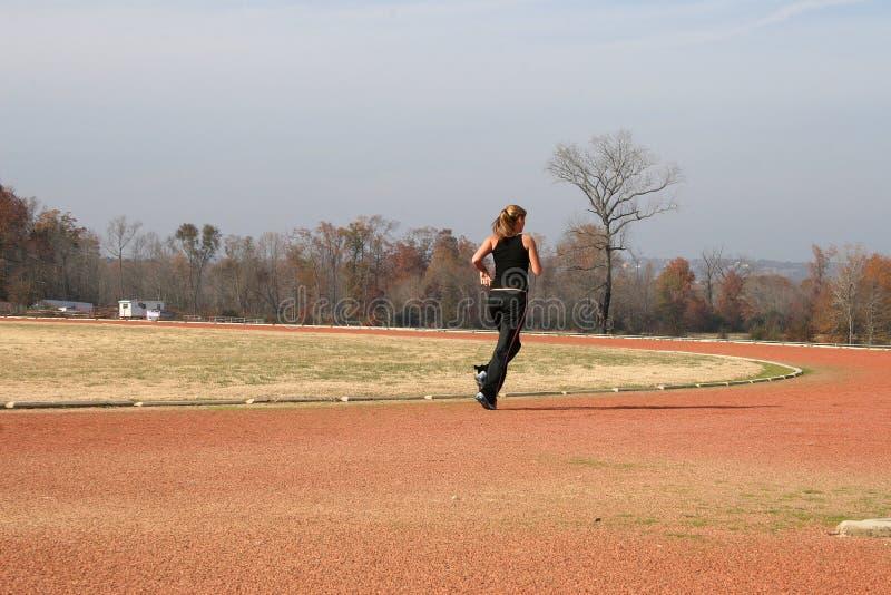 Athletische junge Frau, die an der Bahn läuft