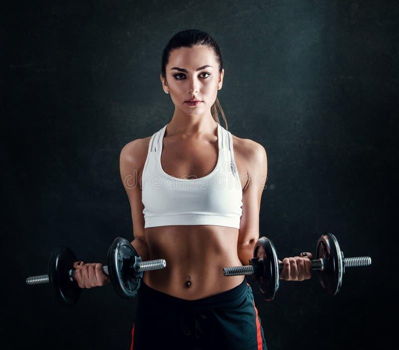 Athletische junge Frau, die ein Eignungstraining gegen schwarzen Hintergrund tut Das attraktive Eignungsmädchen, das oben pumpt,  lizenzfreie stockfotos