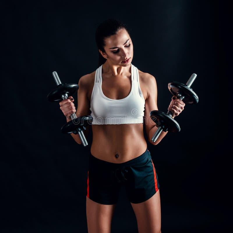 Athletische junge Frau, die ein Eignungstraining gegen schwarzen Hintergrund tut Das attraktive Eignungsmädchen, das oben pumpt,  stockbild