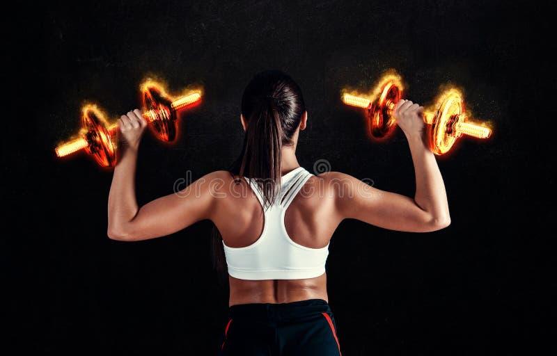 Athletische junge Frau, die ein Eignungstraining gegen schwarzen Hintergrund tut Das attraktive Eignungsmädchen, das oben pumpt,  lizenzfreie stockbilder