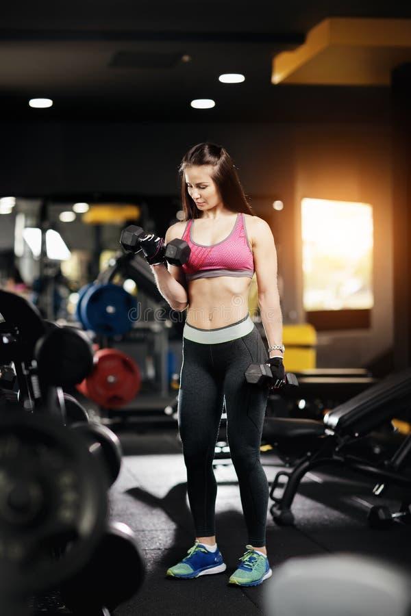 Athletische junge Frau, die schwere Dummkopfübung für Bizeps in der Turnhalle tut stockfotos