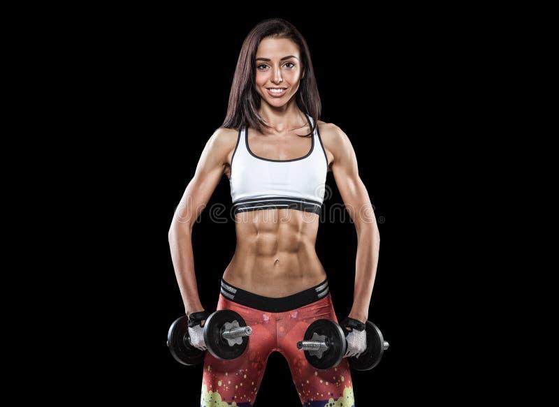 Athletische junge Frau, die Training mit Gewichten auf dunklem backgrou tut stockbild