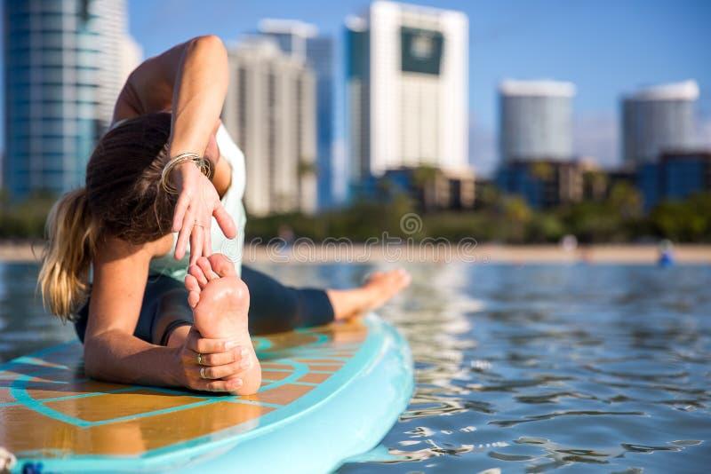 Athletische junge Frau in SUP Yogapraxisseiten-Biegung Haltung im Ala lizenzfreies stockbild