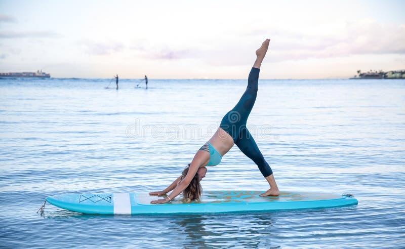 Athletische junge Frau in SUP Yogapraxisseitenbiegungsbein-Aufzug Position stockbilder